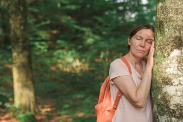 Female environmentalist leaning on tree trunk