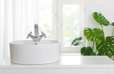 Hygienic wash basin with chrome faucet on bathroom window background