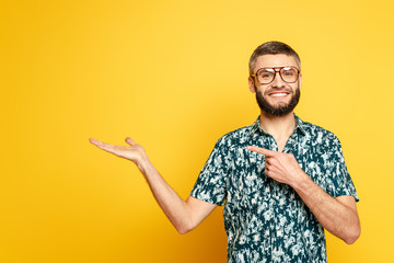 smiling bearded guy in glasses pointing with finger aside on yellow