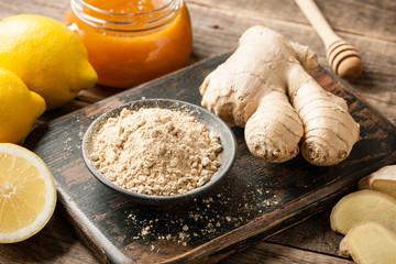 Ginger root, ginger powder, honey and fresh  lemons on wooden table