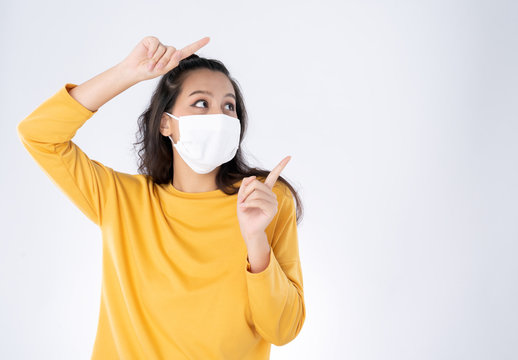 Young happy Asian woman pointing finger hands up to copy space wearing hygienic mask to prevent infection corona virus she wearing yellow sweater shirt shoot in isolated on white background
