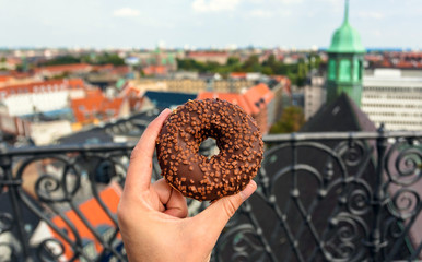 City breakfast on tower of historical city. Donut in hand of hungry person on top point of Copenhagen, Denmark. Leisure in Scandinavia with street food