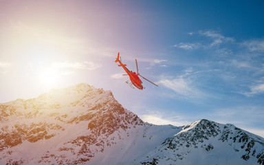 Poster Helicopter Red helicopter flying over the snow covered Alpine mountains during a sunset winter day. Aerial Landscape