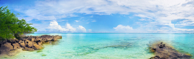 Beautiful tropical panoramic landscape with clear turquoise ocean water, rocks and blue sky with white clouds.