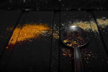 spices on a black background bright seasoning top view