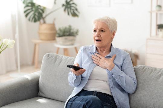 Coronavirus News. Shocked Senior Woman Watching Tv At Home