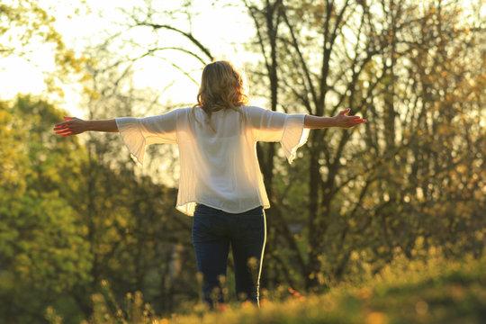 Blonde Frau bei Yogaübung im Park von hinten
