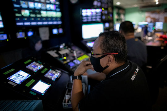 An ABS-CBN employee wearing a protective face mask works in a control room at the broadcast network's headquarters, following orders by telecoms regulator to cease its operations in Quezon