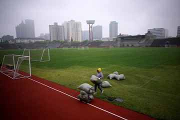 Woman works at a closed soccer field following the coronavirus disease (COVID-19) outbreak, in Shanghai