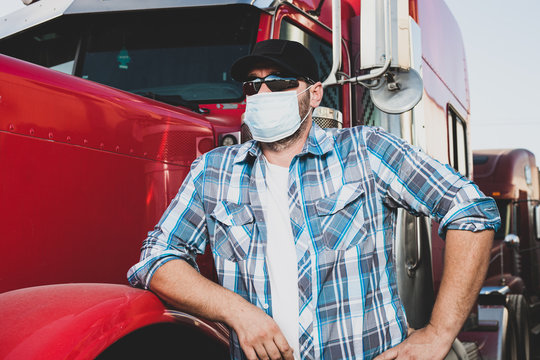 Covid-19 impacting the transportation  industry concept with truck driver wearing safety face mask next to big rig. Confident trucker with airborne disease protective gear. Low angle view portrait.
