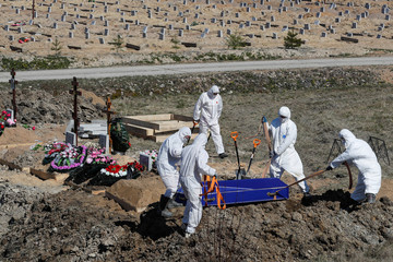 Grave diggers bury a coronavirus disease victim at a graveyard in Saint Petersburg