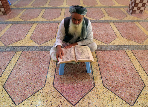 An Afghan man reads the Koran at a mosque during the holy month of Ramadan, amid the spread of the coronavirus disease (COVID-19), in Jalalabad