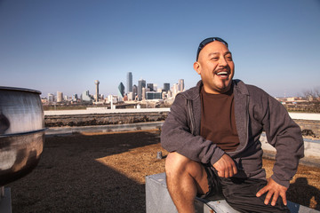 Laughing man sitting on rooftop, Dallas, Texas, USA
