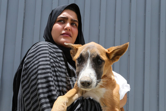 A Saudi woman carries her dog at Riyadh's animal shelter, dedicated to caring for animals amid fear that cats and dogs might contract or transmit the coronavirus disease (COVID-19), Riyadh