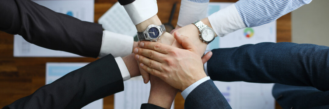 Group men in suits hold out their hands in unity