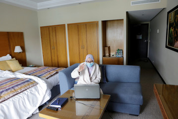 Nurse anaesthetist Teimi Hakima uses a laptop to make a video call and speak with her family in her room at hotel Dawliz in Sale