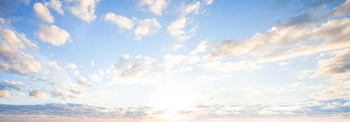 Blue sky clouds background. Beautiful landscape with clouds and orange sun on sky Wall mural