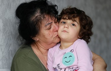 Ayse Mehmet kisses her three-year-old granddaughter, also named Ayse, at her home in Enfield