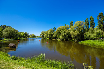 Fototapete - Beautiful rural landscape. Blue sky and green trees reflecting in the water, boats float on the calm water of the river.