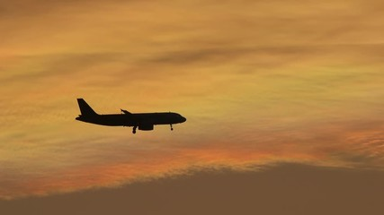 Fototapete - Silhoutte of plane flying over sunset sky background