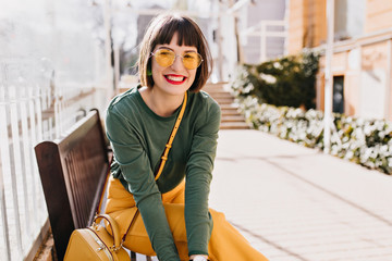 Laughing elegant woman chilling after spring walk. Outdoor photo of lovely brunette lady sitting on bench.