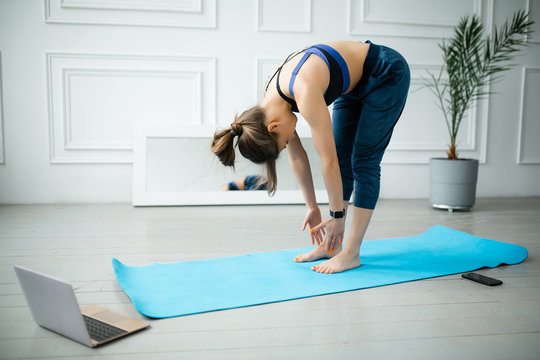 Yoga instructor shows the right laptop yoga exercises online. Stretching the chest and back for stretching the back muscles