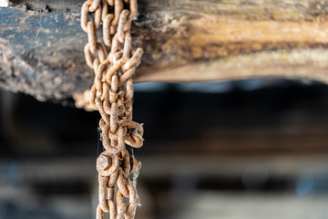 Old rusty chain hanging from a rustic wooden beam.