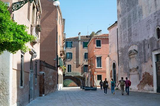 Тourists walking down a beautiful street toward a bridge in Venice. View to bridge Ponte Storto near the Church of San Marcuola, Cannaregio district, Venice, Italy