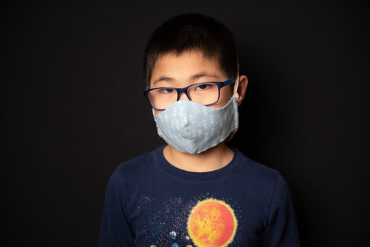 Portrait of Asian boy in glasses wearing cloth face mask