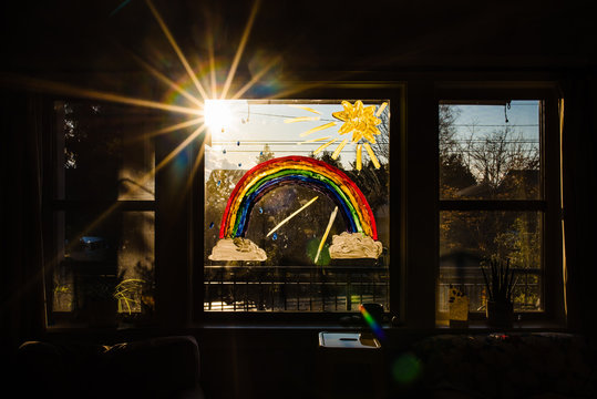 Rainbow with sun and clouds on window for encouragement during pandemic