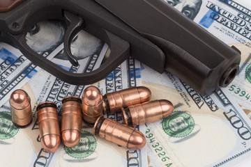 gun with ammo on 100 dollar bills