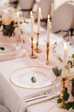Wedding dinner table reception. Close-up of wildcard with gold beads, transparent glass. Runner of pink silk. Candles in golden candlesticks and flowers in the center of the table.