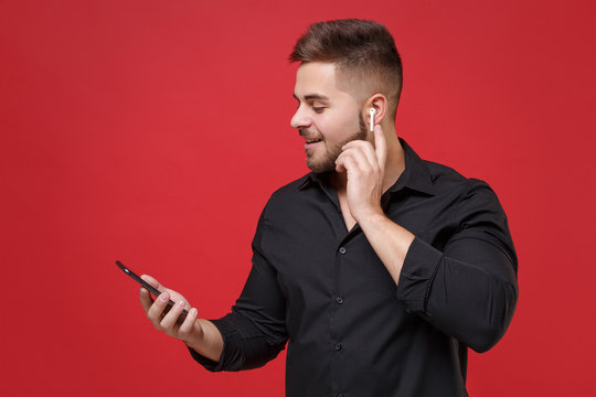 Smiling young bearded guy in classic black shirt posing isolated on bright red wall background studio portrait. People emotions lifestyle concept. Mock up copy space. Using air pods and mobile phone.