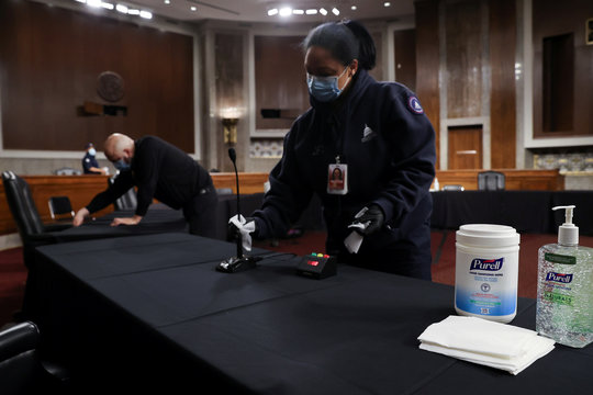 Workers clean between Senate committee hearings on Capitol Hill during coronavirus outbreak in Washington