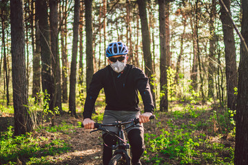 Cyclist wearing pollution mask. Young guy in respirator with filter pm 2.5 with ride on bike in park. Covid 19 Quarantine Sport. Mountain biker riding cycling in forest. mountainbiker on a trail