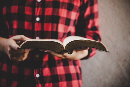 girl hands while reading the Bible.