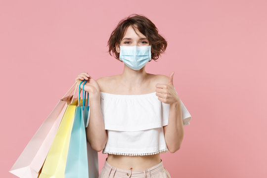 Smiling young woman girl in summer clothes sterile face mask hold package bag with purchases isolated on pastel pink background. Shopping discount sale concept. Mock up copy space. Showing thumb up.