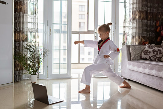 Taekwondo girl in kimono with white belt exercising at home in living room. Online education during coronavirus covid-19 lockdown, self isolation and social distancing concept.