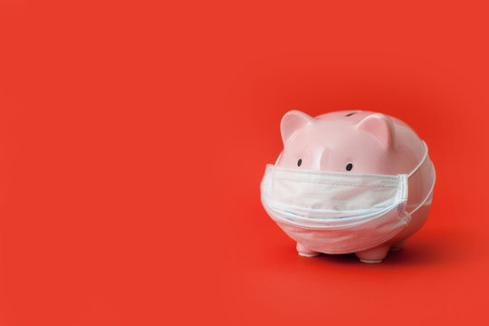 Pink piggy bank with a medical mask is half-sided on a red background