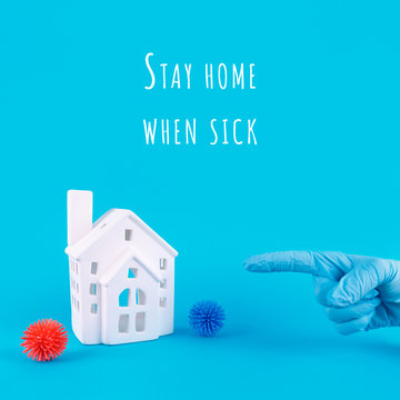 Hand in disposable glove points to cute little house with Stay home when sick wording. Epidemic, respoiratory desease, social isolation, coronavirus COVID-19 concept. Square format with place for text