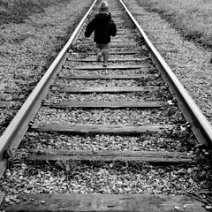 Spoed Fotobehang Spoorlijn Rear View Of Child Walking On Railroad Track