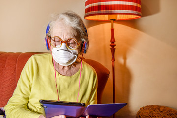 Trendy elderly woman in a respiratory mask and headphones with a e-book in hands stay at home on the sofa. Entertainment on quarantine, isolation. Epidemic Coronavirus COVID-19. Senior Health