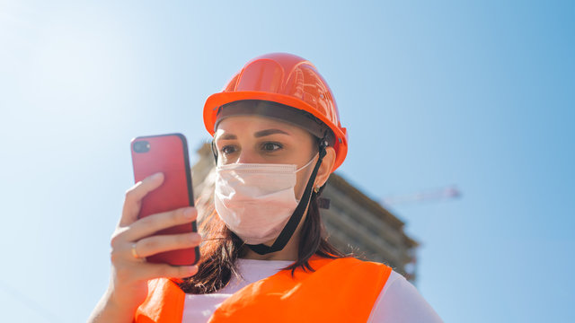 Female construction worker in overalls and medical mask recording audio message on smartphone on background of house under construction. Concept of threat of coronavirus epidemic infection.