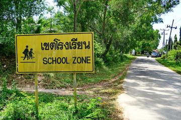Panneau bilingue anglais-thai au bord de la route: School Zone. Thailande.