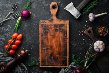 Fototapete - Black kitchen background. Kitchen board, vegetables and spices on a black stone background. Top view.