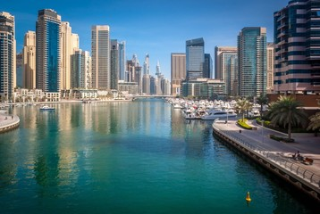 Tuinposter Dubai River Amidst Modern Buildings In City Against Sky