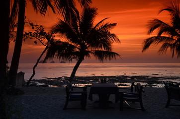 Fototapeta Zachód słońca w romantycznej scenerii na egzotycznej plaży z palmami w Tajlandii obraz