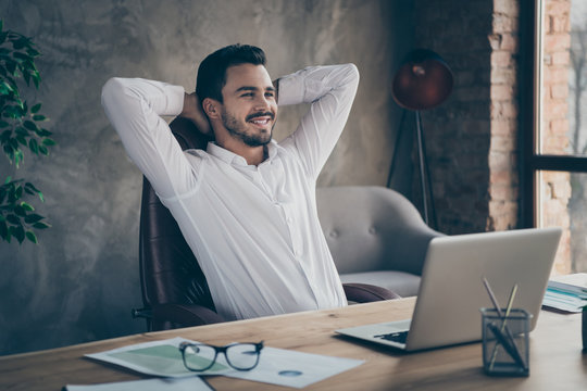 Portrait of his he nice attractive cheerful cheery confident man top manager specialist shark sitting in chair having rest at modern loft brick industrial style interior workplace station