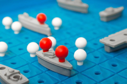 Battleship, board game. Sea battle. Toy ships on a plastic board. Perfect hit. Victory or defeat. Blue background, blur.