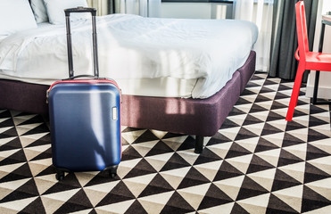 suitcase stands by the bed in the hotel room. Concept on the theme of arrival in the hotel room